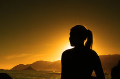Sunset silhouette. Of female with ocean in background Royalty Free Stock Photography