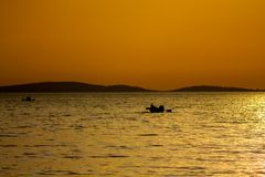 Sunset silhouette of a boat on the lake Stock Images