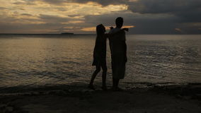 Sunset silhouette of couple on the beach stock video