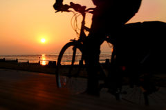Sunset silhouette cyclist. Photo of a sunset over the kent coast of whitstable with silhouetted cyclist stock image