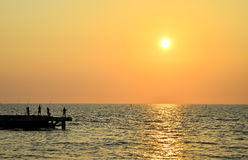 Sunset with silhouette of fisherman. Sunrise over the sea with silhouette of man fishing Royalty Free Stock Images