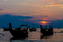 Sunset silhouette of fishing boat on sea beach in Thailand. Scenic landscapes of sea resort with fisherman boat and nature at sunset, sunrise and dusk Stock Photos