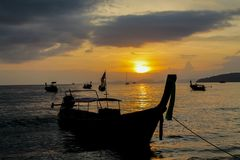 Sunset silhouette of fishing boat on sea beach in Thailand. Scenic landscapes of sea resort with fisherman boat and nature at sunset, sunrise and dusk Royalty Free Stock Photo