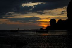 Sunset silhouette of fishing boat on sea bay in Thailand. Sunset silhouette of fishing boat on sea beach in Thailand. Scenic landscapes of sea resort with Royalty Free Stock Photography
