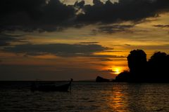 Sunset silhouette of fishing boat on sea beach in Thailand. Scenic landscapes of sea resort with fisherman boat and nature at sunset, sunrise and dusk Royalty Free Stock Image