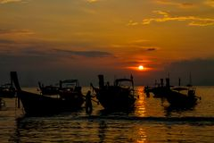 Sunset silhouette of fishing boats on sea beach in Thailand. Scenic landscapes of sea resort with fisherman boat and nature at sunset, sunrise and dusk Stock Image