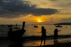 Sunset silhouette of fishing boats and tourist on sea beach in Thailand. Sunset silhouette of fishing boats and tourist making selfy on sea beach in Thailand Royalty Free Stock Photo
