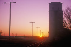Sunset silhouette of grain silo beside train tracks, KS Royalty Free Stock Photos