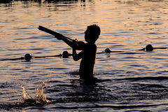 Sunset silhouette of happy child enjoys water games in the pool Royalty Free Stock Image