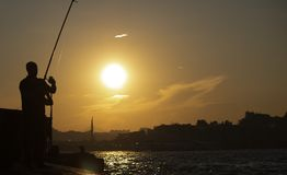 Sunset silhouette of holding fish stock photos
