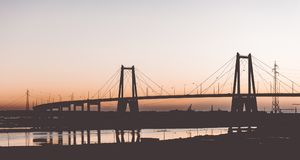 Silhouette of the suspension concrete bridge on a sunset stock photography