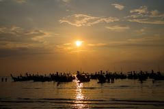 Sunset silhouette of long tail boat at sea bay in Thailand. Scenic landscapes of sea resort with fisherman boat and nature at sunset, sunrise and dusk stock photography