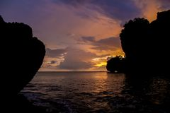 Sunset silhouette of rocks in bay in Thailand Stock Photo