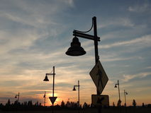 Sunset silhouette. A neat perspective of street signs and light posts, silhouetted by the setting sun Royalty Free Stock Photo