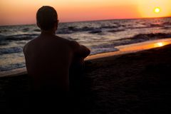 Man looks at the sunset on the beach. silhouette of a man who sits on the sand near the sea, in the rays of the setting sun near t. Sunset Silhouette with the Stock Photography