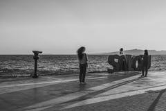 Sunset with silhouette of people at the coastline Costa Dorada, promenade Salou, black white