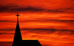 Church spire - religious church building silhouetted. Sunset silhouette of religious building with cross Stock Photography