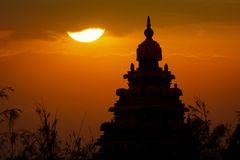 Sunset silhouette of shore temple, Mahabalipuram, Tamil Nadu. A beautiful golden sunset behind one of the temple towers of Mahabalipuram. Mahabalipuram is a Stock Photo