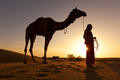 Sunset Silhouette of a woman and her camel. Stock Image