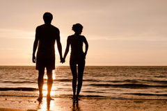 Sunset silhouette of young couple in love holding Royalty Free Stock Photo