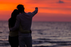 Sunset silhouette of young couple in love hugging at beach Royalty Free Stock Photo