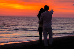 Sunset silhouette of young couple in love hugging at beach Stock Photo