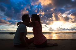 Sunset silhouette of young couple in love hugging and kissing at beach Royalty Free Stock Photos