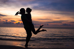 Sunset silhouette of young couple in love hugging Stock Image