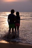 Sunset silhouette of young couple in love hugging Stock Images