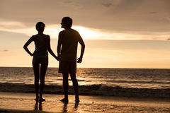 Sunset silhouette of young couple in love walking Stock Photos