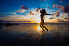 Sunset silhouette of young fit woman jumping at beach Royalty Free Stock Images