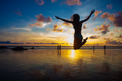 Sunset silhouette of young fit woman jumping at beach Stock Photo