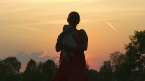 Sunset Silhouette: Young mother holding her baby boy child in city park standing in front of setting sun and vivid. Orange sky - Family values warm color summer stock footage