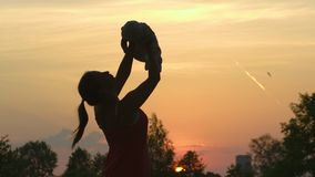 Sunset Silhouette: Young mother holding her baby boy child in city park standing in front of setting sun and vivid