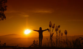 Sunset silhouette Young woman feeling to Freedom and Relax Stock Image