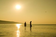 Sunset Silhouettes. A silhouette of two figures in the ocean as the sun sets behind them Stock Photos