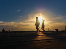 Sunset silhouettes. Of a man and woman walking, and a man fishing royalty free stock photo