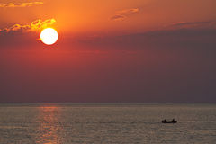Sunset with silhouettes of paddling boat. With two men Royalty Free Stock Images