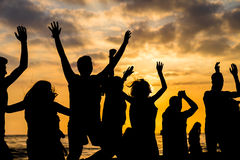 Sunset with silhouettes. People celebrating and jumping on the beach royalty free stock image
