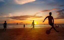 Sunset silhouettes playing beach football Stock Photography