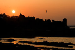 Sunset silhouettes at St Andrews castle stock image