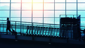 Sunset Silhouettes of Travelers in Airport. Beautiful view walkway of an airport with travelers and commuter stock video