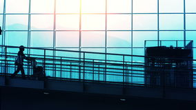 Sunset Silhouettes of Travelers in Airport. Sunset airport terminal hall. Walking travelers silhouettes stock footage