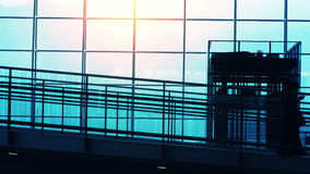 Sunset Silhouettes of Travelers in Airport. Airport terminal hall. Walking travelers silhouettes stock video