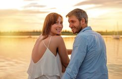 Sunset sitting lake couple. Smiling royalty free stock photo