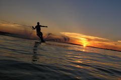 Sunset Ski. A waterskier carving a turn with the sun setting behind Stock Images
