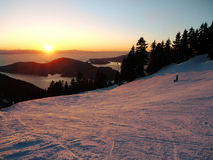 Sunset on the ski slope. Located in West Vancouver BC Cypress Resort has  views of the mountain and the Pacific Ocean. Pine trees and a lonely snowboarder Stock Images