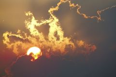 Sunset sky with clouds.clouds partially cover the sun. royalty free stock photography