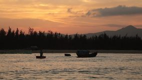 Sunset Sky With Fishing Boats. A fiery orange evening sky looking out over the south China sea in Vung Lam Bay Vietnam. With fishing boat silhouettes coming and stock video