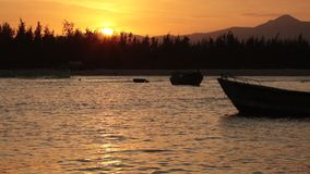 Sunset Sky With Fishing Boats. A fiery orange evening sky looking out over the south China sea in Vung Lam Bay Vietnam. With fishing boat silhouettes coming and stock video footage